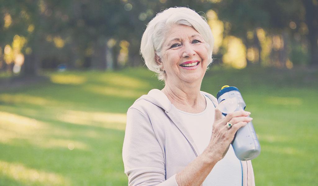 smiling elderly woman holding a water bottle outside