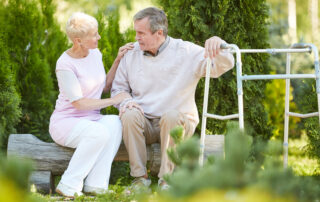 Older man with walker sitting on park bench with an older woman smiling
