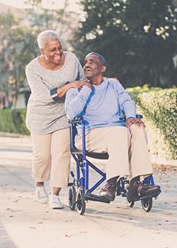 Senior woman pushing husband in wheelchair outside on concrete sidewalk