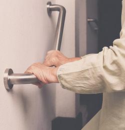 Elderly woman using handrail to walk