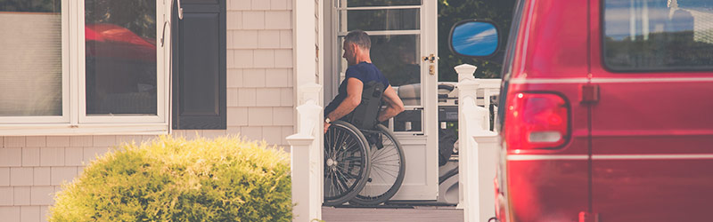 Man in a wheelchair using a ramp outside of home to enter front door