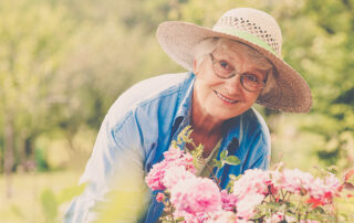 smiling elderly woman in garden with pink flowers