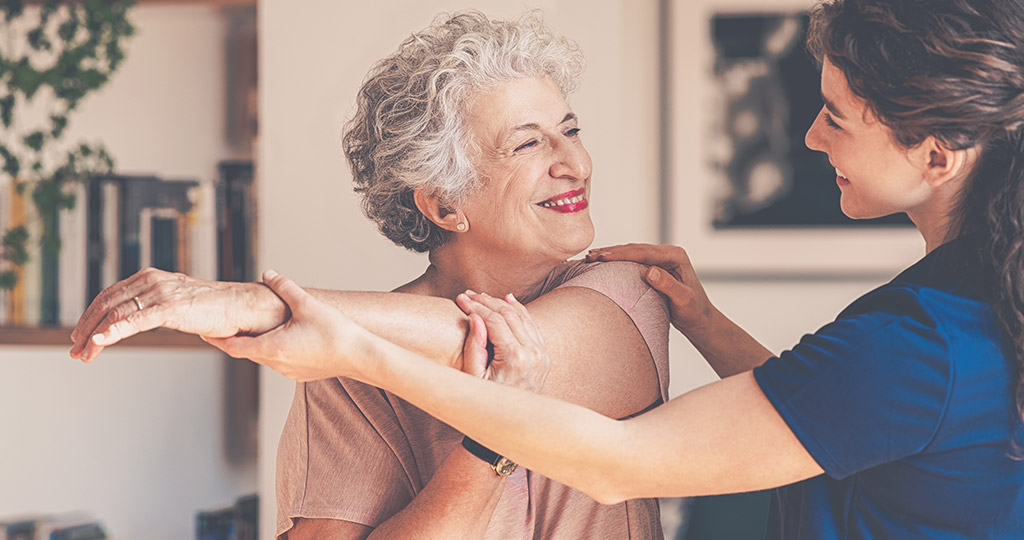 Caregiver helping senior woman stretch her arm across her body