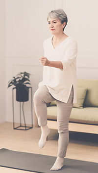 Woman marching in place in living room for exercise