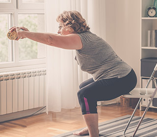 Woman exercising in living room by sitting and standing by chair