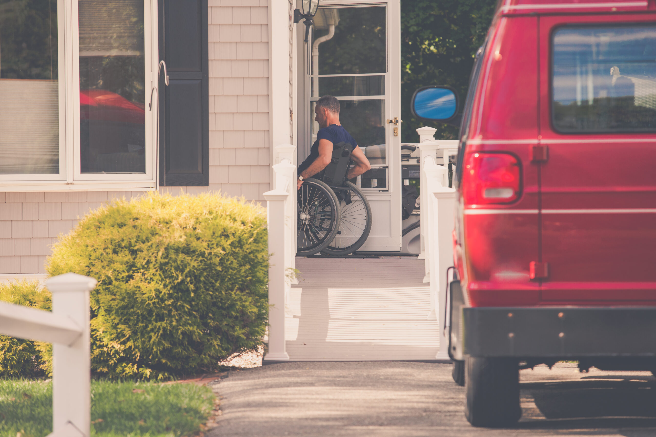 Red van with man in wheel chair entering home after leaving car