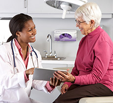 Female doctor talking over notes with an elderly woman