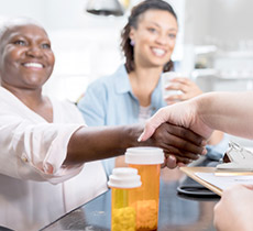 Senior woman with adult daughter shaking hands with doctor