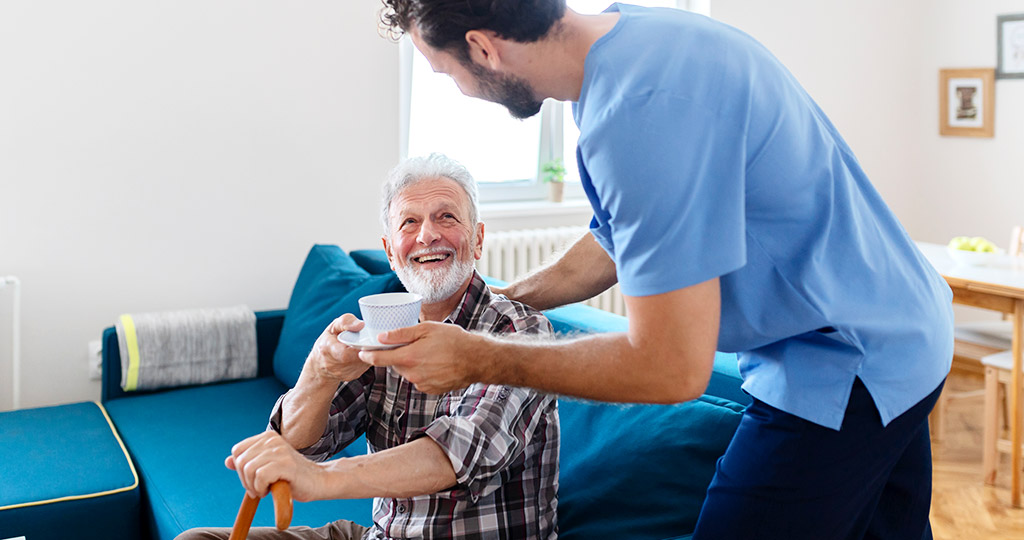Caregiver handing tea to an elderly man sitting on a couch with a cane
